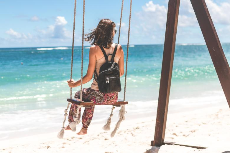 woman-sitting-on-seashore-swing-1027079